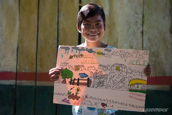 Acélio Augusta com o desenho que fez, retratando a aldeia Dace Watpu, que agora tem placas solares para gerar energia. (©Otávio Almeida/Greenpeace)